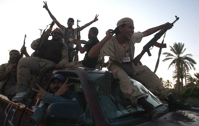 Riding to victory:A group of Libyan rebels smile and make peace signs as they progress into Tripoli yesterday