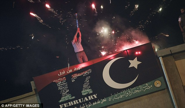 Celebration: A man on the roof of a building in Benghazi fires a flare into the air as other fireworks go off around him
