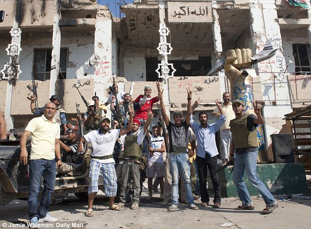 Taking a look round: This group of Tripoli residents could hardly believe their eyes when they entered Gaddafi's compound yesterday