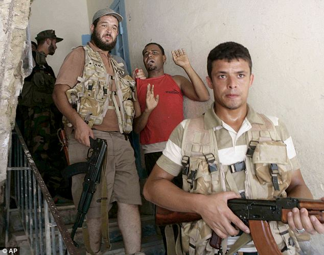 Rebel fighters arrest a suspected Gaddafi loyalist during search of Tripoli apartments
