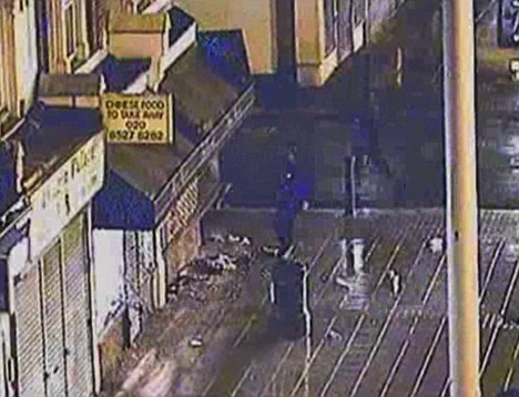 Brave: Black-clad, armoured riot police arrive on the scene at Waltham Forest and give chase during the riots