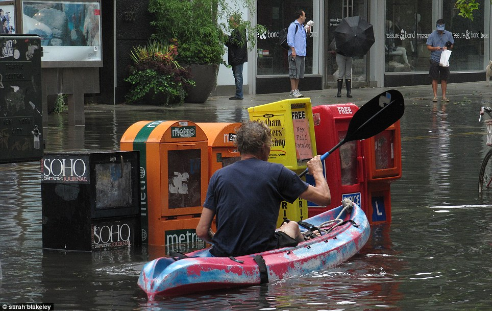 Making the best of it: A man kayaks down West Broadway in Manhattan as flood waters ripple through Manhattan's trendy SoHo neighbourhood