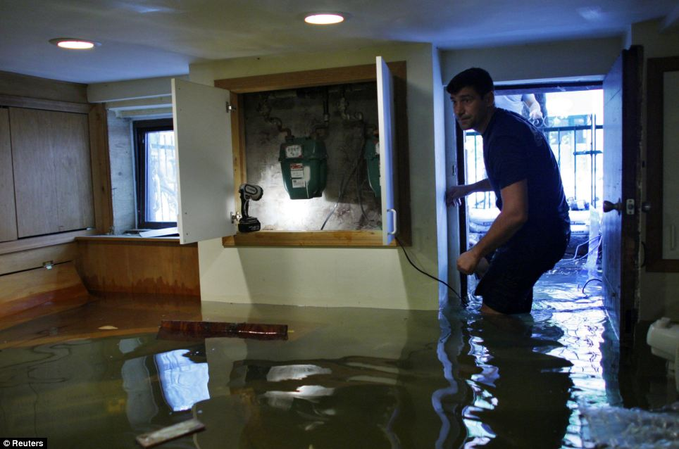 Submerged: Andre Kozlov, 38, walks through his flooded basement after the pass of Hurricane Irene in Hoboken, New Jersey