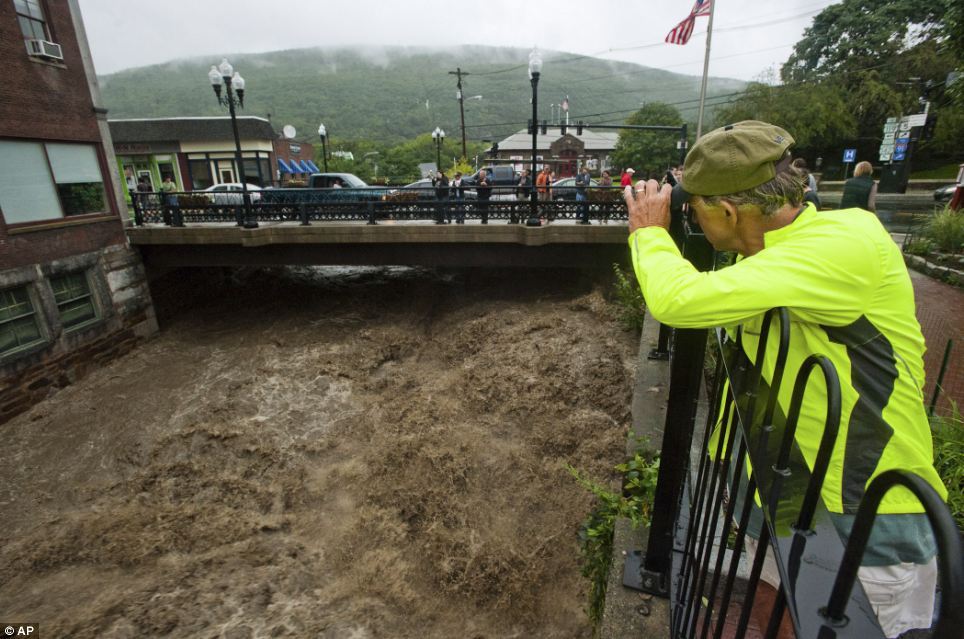 Roaring: Mel Martin joins a crowd watching the raging Whetstone Brook surge over the falls in downtown Brattleboro, Vermont