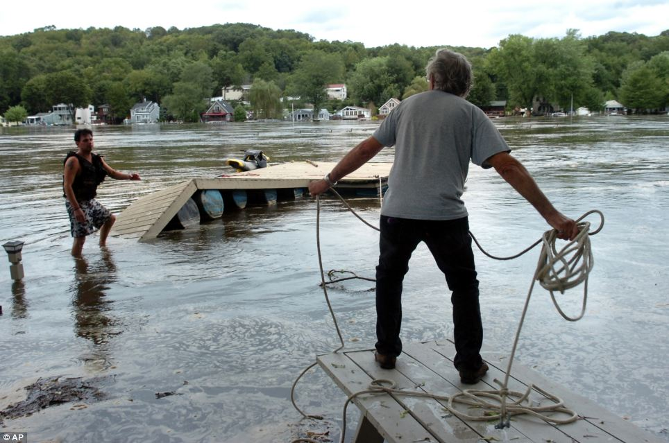 Securing: Rich Machnicz throws a rope to his son Shawn as they try to secure a floating dock on the Housatonic River behind their home in the Maples neigborhood of Shelton, Connecticut