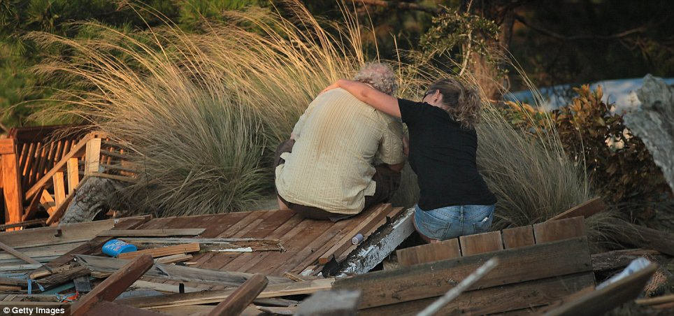 Rubble: Billy Stinson, left, is comforted by neighbour Lisa Morrisette while he sits next to a pile of debris that was once his cottage in Nags Head, North Carolina