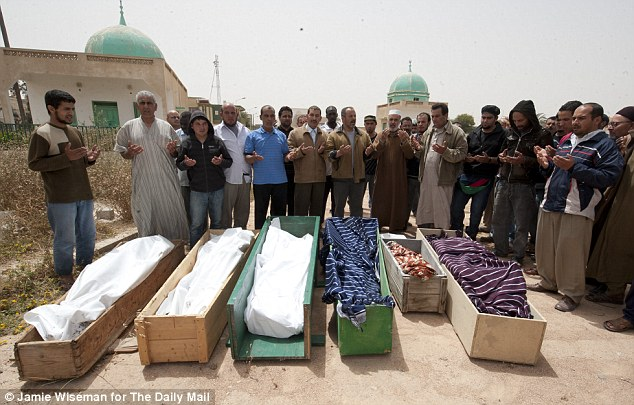 Hundreds of civilians died in the siege: Here seven members of the Al Nour family - including Abdul Mufta, eight, and Nadia, five - are buried after their house was bombed by Gaddafi's troops