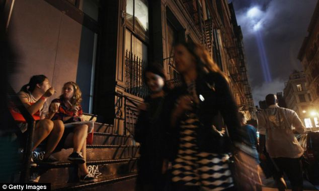 Business as usual: New Yorkers gather outside a gallery for Fashion Night in Soho as the Tribute in Light sends twin beams to the heavens in the background