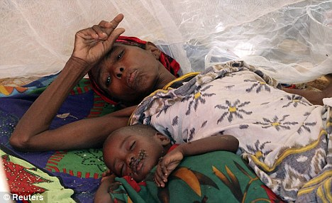 Devastating: A woman and her malnourished child rest inside a ward at Banadir hospital in Mogadishu. The UN warned this week that 750,000 people could die of starvation in the country