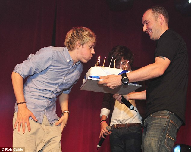 Unsuspecting: Niall had no idea what was coming and was happy to blow out the candles on his special cake