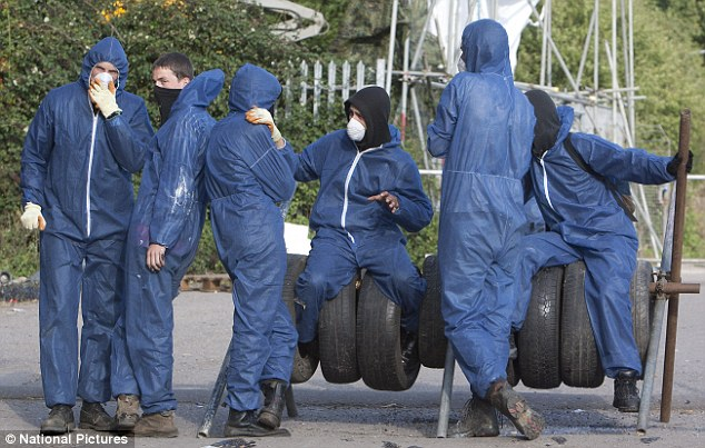 Waiting around: A group of young anarchists sit on tyres wearing their blue boiler suits to mark them out from ordinary protesters