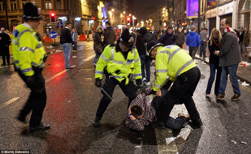 Batons raised: Three officers restrain a youth whose evening has taken a turn for the worse