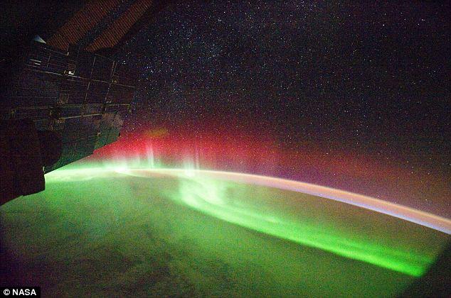 Luz fantástica: Esta impresionante imagen de la Estación Espacial Internacional muestra un color verde brillante y aurora roja sobre la tierra causada por las llamaradas solares