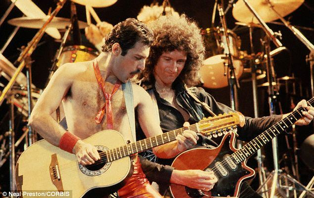 Ultimate showman: Freddie Mercury with Queen guitarist Brian May playing guitars in front of Roger Taylor's drums in the 1980s