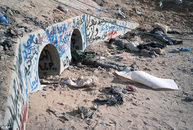 Battleground: Bodies of suspected Gaddafi loyalists lie outside the storm drains their leader was captured