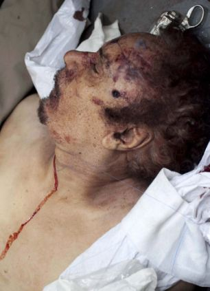 Brutal end for tyrant who exported terror: Gaddafi's body is displayed, clearly showing a bullet hole in his head