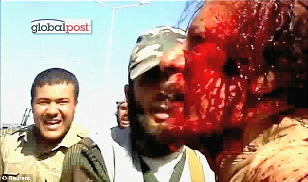 Blood pours from a wound above Gaddafi's left temple. The rebels jeer and laugh as they hurl insults at him. 'Shut up, dog', is how the stubborn tyrant responds
