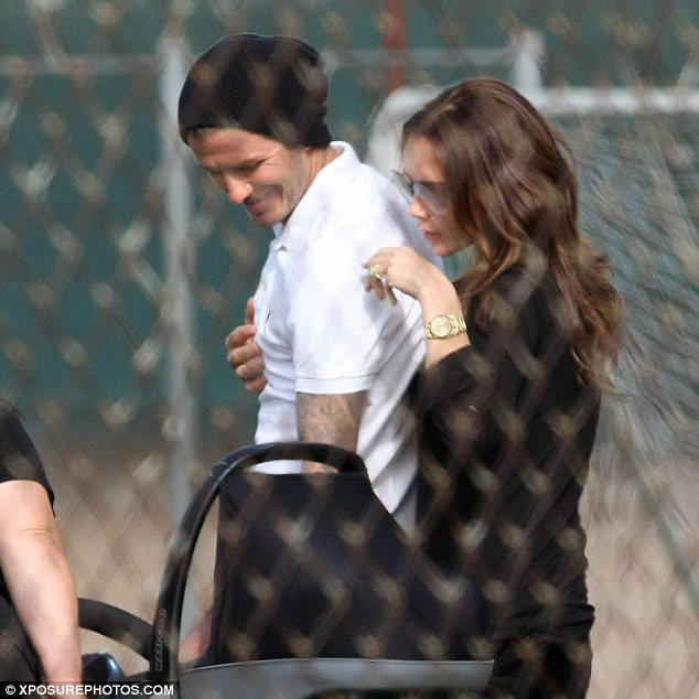 Family fun: Victoria and David Beckham enjoyed a cuddle as they watched their sons play football, having their whole family together