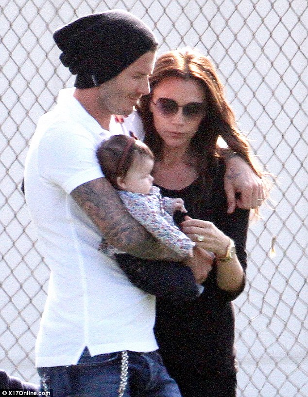 Family moment: David and Victoria share a cuddle with baby Harper at a football match in Long Beach