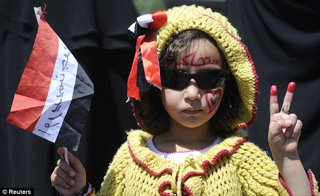 Hoping for victory: A young girl holding a Yemeni flag makes a peace sign during a protest rally in Sanaa