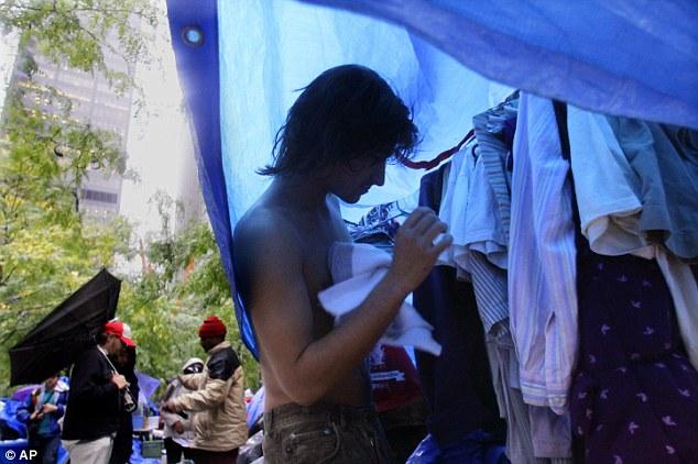 Cambiar: Mike Esperson, 22 años, de Queens, Nueva York, que se despertó para encontrarse empapada por la lluvia en el campo Ocupar pared protesta callejera, recoge sin ropa donada en el vestidor Zuccotti Park