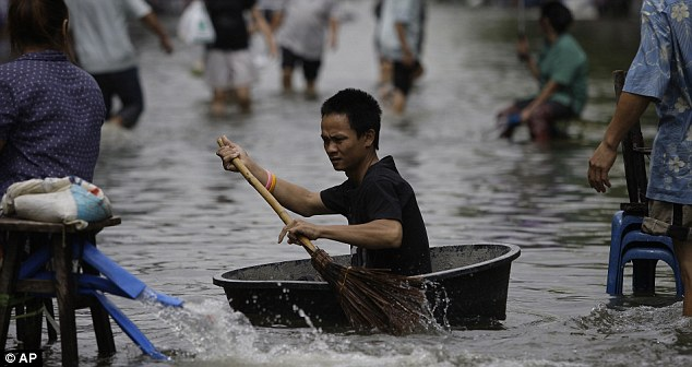 Water traveller: A Thai uses a broom to paddle a big plastic container along one of Bangkok's flooded streets