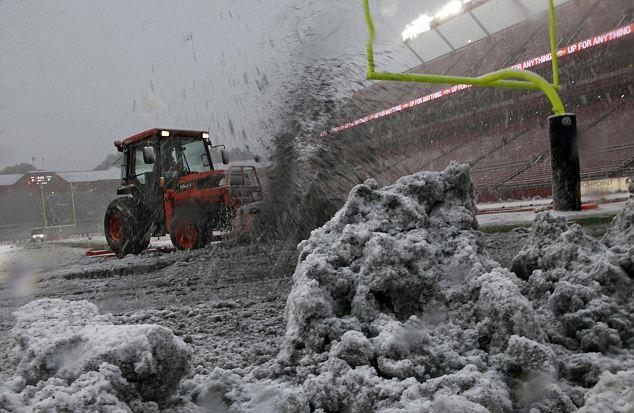 Tractor para el rescate: los trabajadores tratan de despejar la nieve que caen del campo antes de un partido de fútbol americano universitario NCAA entre Virginia Occidental y Rutgers en Piscataway, Nueva Jersey hoy
