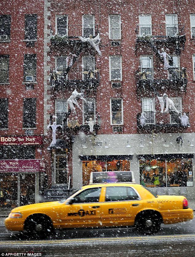 Macabro: Un taxi conduce más allá de una casa decorada de Halloween-como la nieve cae en Nueva York hoy