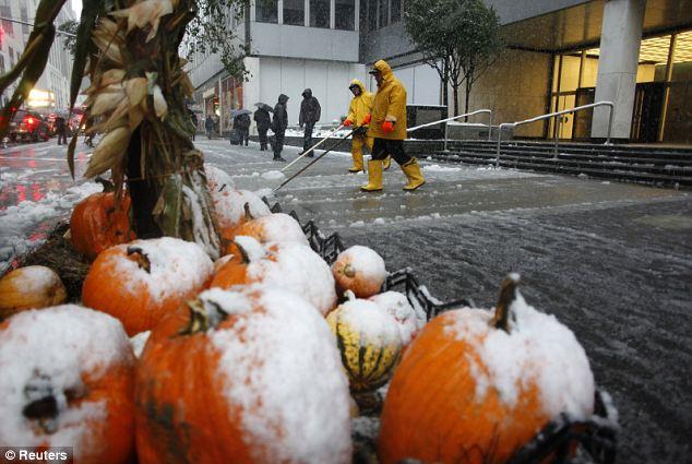 Calabaza helada: nieve Trabajadores clara de las aceras como una pantalla decorativa de calabazas estaba cubierto de nieve hoy en Nueva York
