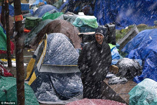 Traicioneros: Un manifestante búsquedas para su tienda en forma de nieve caídas en torno a él en el Bajo Manhattan Parque Zuccotti