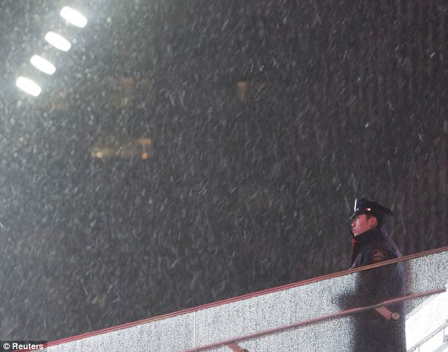 En la noche: Un oficial de Policía de Nueva York Departamento de hace guardia en Times Square cuando la nieve se reduce