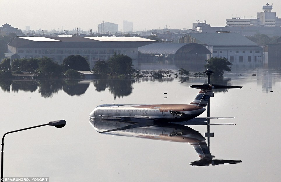 Submerged: A decommissioned Thai jetliner sits on the runway at Don Mueang Airport in Bankgkok, completely surrounded by floodwaters