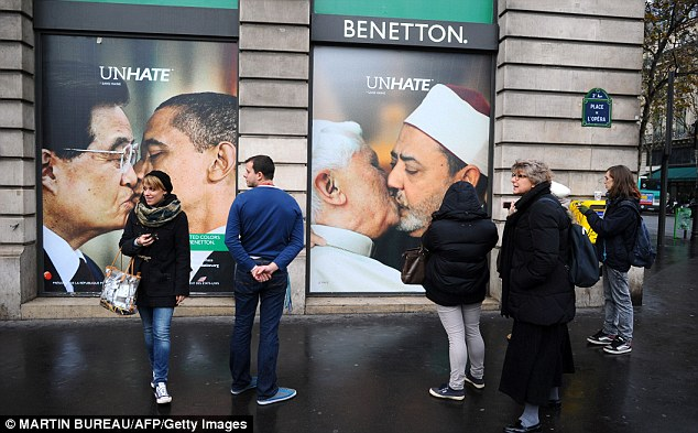 Attention: People look at a Benetton clothing store window in Paris which is covered by posters as part of its new provocative campaign