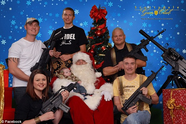 One for the family album: Santa holds a baby as he is surrounded by AK47s, grenade launchers and assault rifles