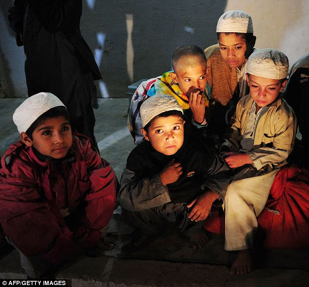 Freed: Young Pakistani students sit a room after being rescued following a police raid on Madrassa Zakarya in Karachi last night