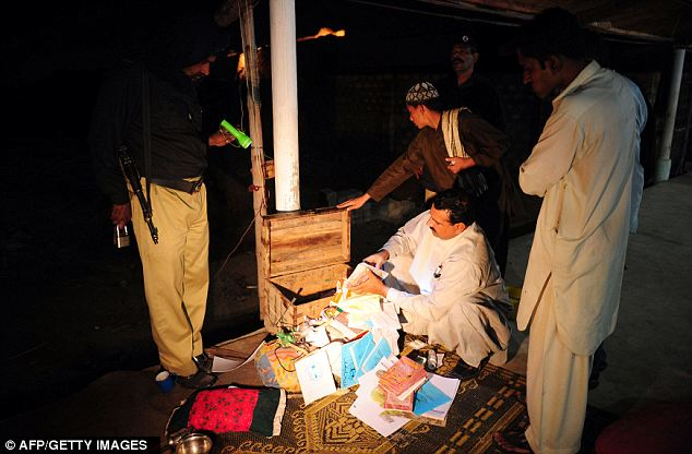 Pakistani policemen examine documents found at the Islamic seminary. One cleric and two others were arrested at the scene