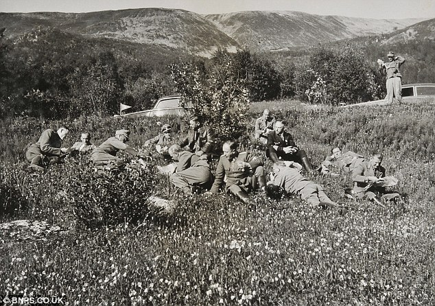 Picnic: German officers relaxing and enjoying a picnic in a flowery meadow in Norway in the summer of 1942