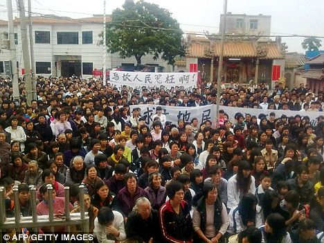 Occupy Wukan: This cell phone picture, taken by a Wukan villager, shows thousands of residents carrying a banner saying 'Wukan's people were treated unjustly' as they hold a protest against land seizures by local officials
