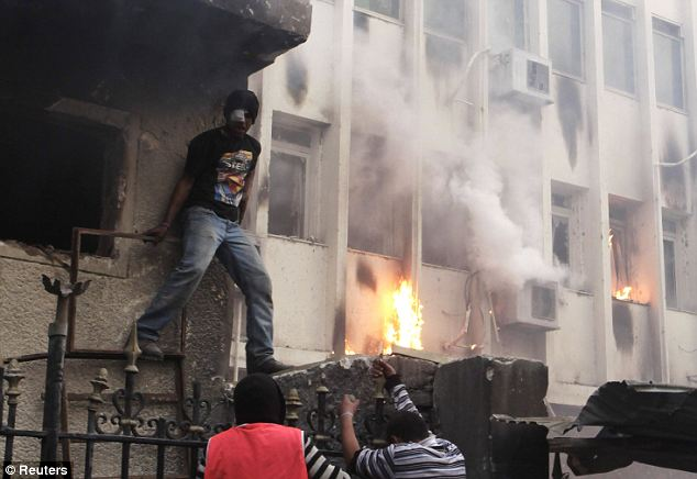 Direct assault: Protesters climb over the fence of a burning cabinet building which was part-destroyed in Cairo