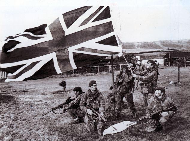Royal Marines en San Carlos elevar la bandera del Reino Unido durante la Guerra de las Malvinas
