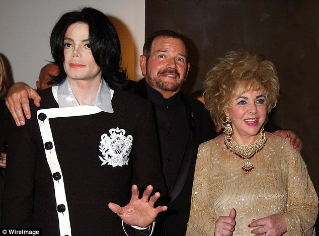 Close friends: Klein (centre) poses with friends and clients Michael Jackson and Elizabeth Taylor at a charity event