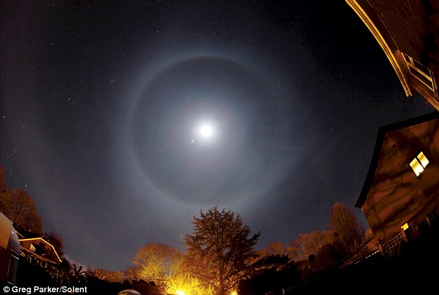 Stargazer Professor Greg Parker captured a rare 'lunar halo' - an optical effect caused by light refracting off millions of ice crystals in the clouds of the night sky
