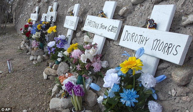 Marking the spot: A memorial of flowers and crosses across the street from the Safeway in Tucson where one year before a shooting left six dead and 13 injured