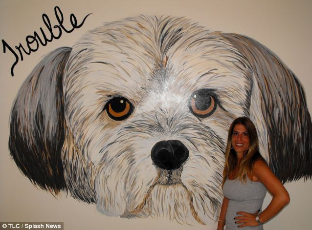 Beloved pet: Danielle Tarantola paid £32,000 to have Trouble cloned, she is pictured in her New York home with the massive portrait she had painted of him after his death