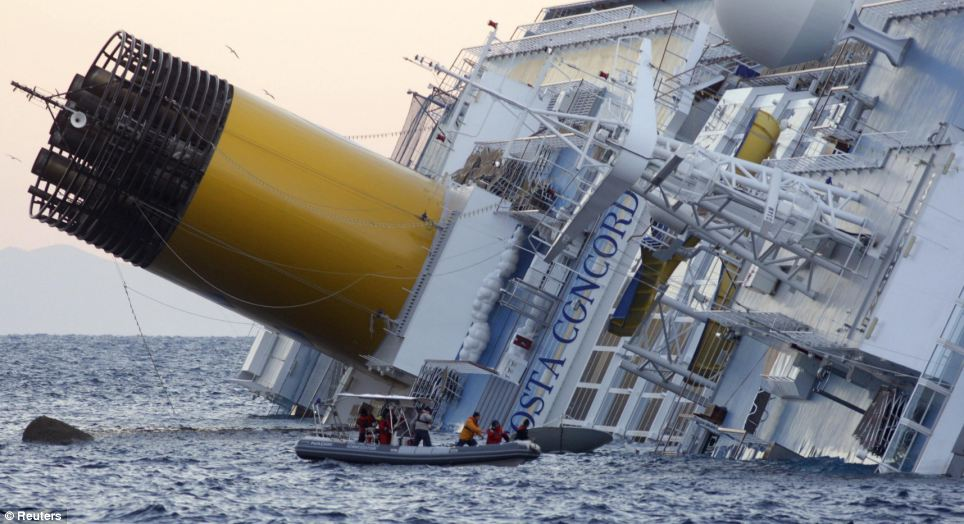 Sunk: Rescuers hunt desperately for survivors yesterday as the Costa Concordia remains lying on its side
