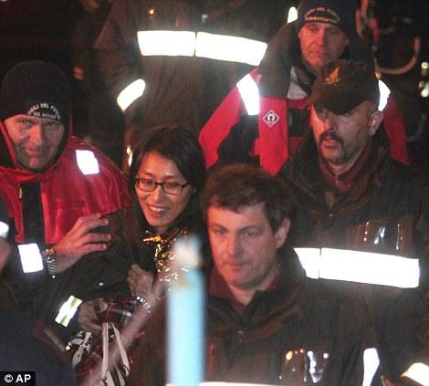 Un passager de la Corée du Sud, au centre, promenades avec les pompiers italiens après avoir été sauvé