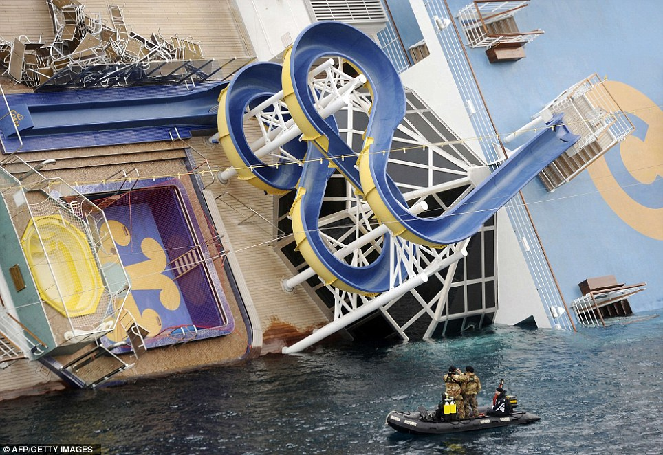 Sliding into the sea: Military rescuers patrol next to the cruise ship. A water slide can be seen here on its side and above sun lounger chairs are still on deck after it ran aground and keeled over