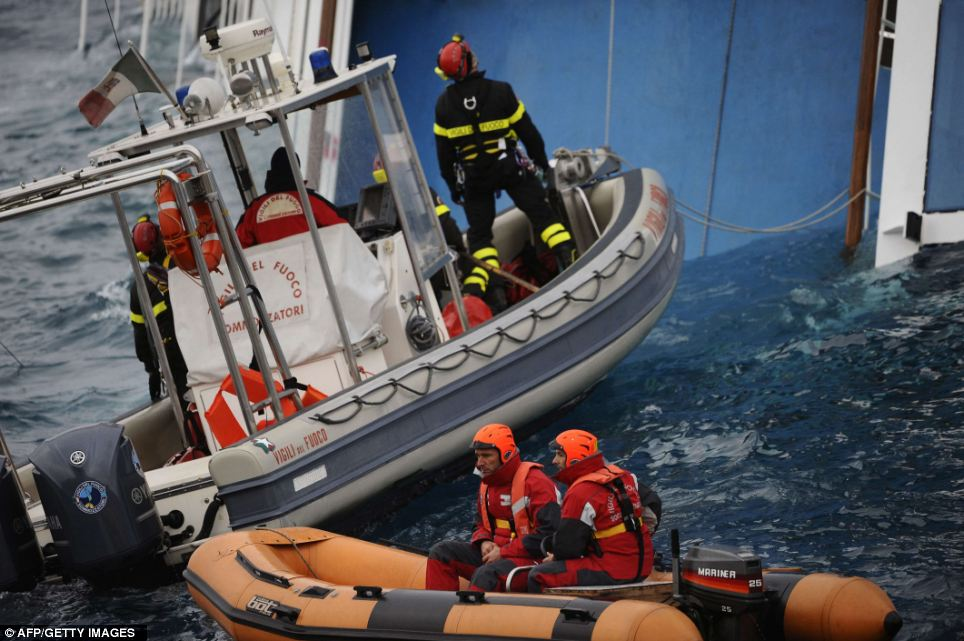 Firemen search for missing people in and around the partially submerged Costa Concordia cruise ship