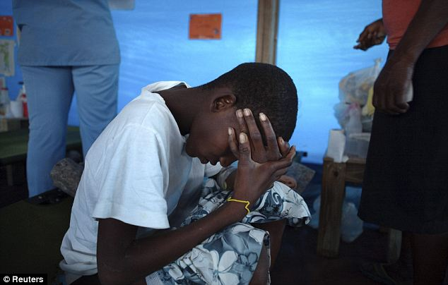 Fifteen-year-old cholera patient Jonas Florvil sits on a cot in a nearly empty ward at a Samaritan's Purse cholera treatment center in the Cite Soleil neighborhood of Port-au-Prince, January 8, 2011