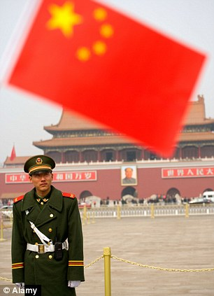 A Chinese soldier stands guard outside Tiananmen Gate in Beijing as the red flag flies